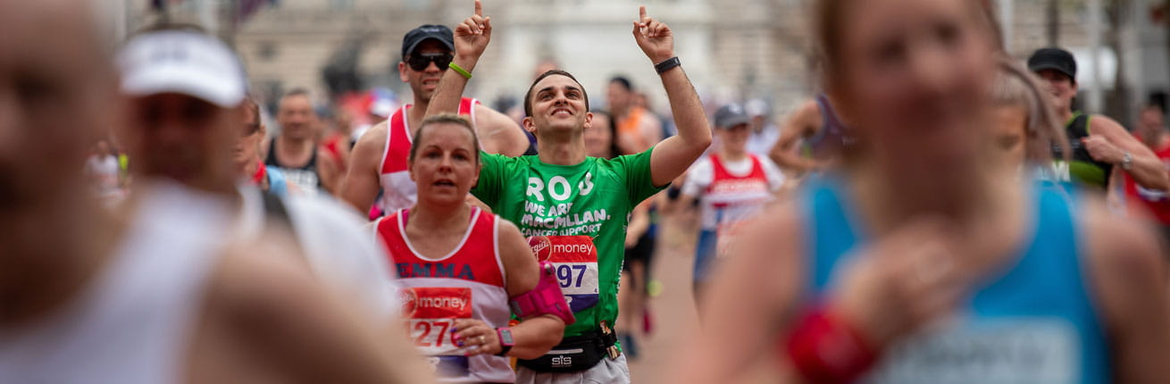 A macmillan charity runner points to the sky as he nears the finish line