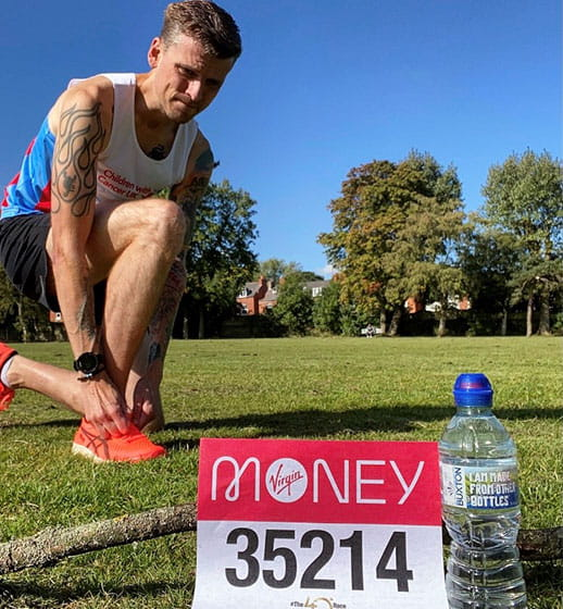 A runner with a bottle of Buxton Natural Mineral Water and their Virgin Money London Marathon running number