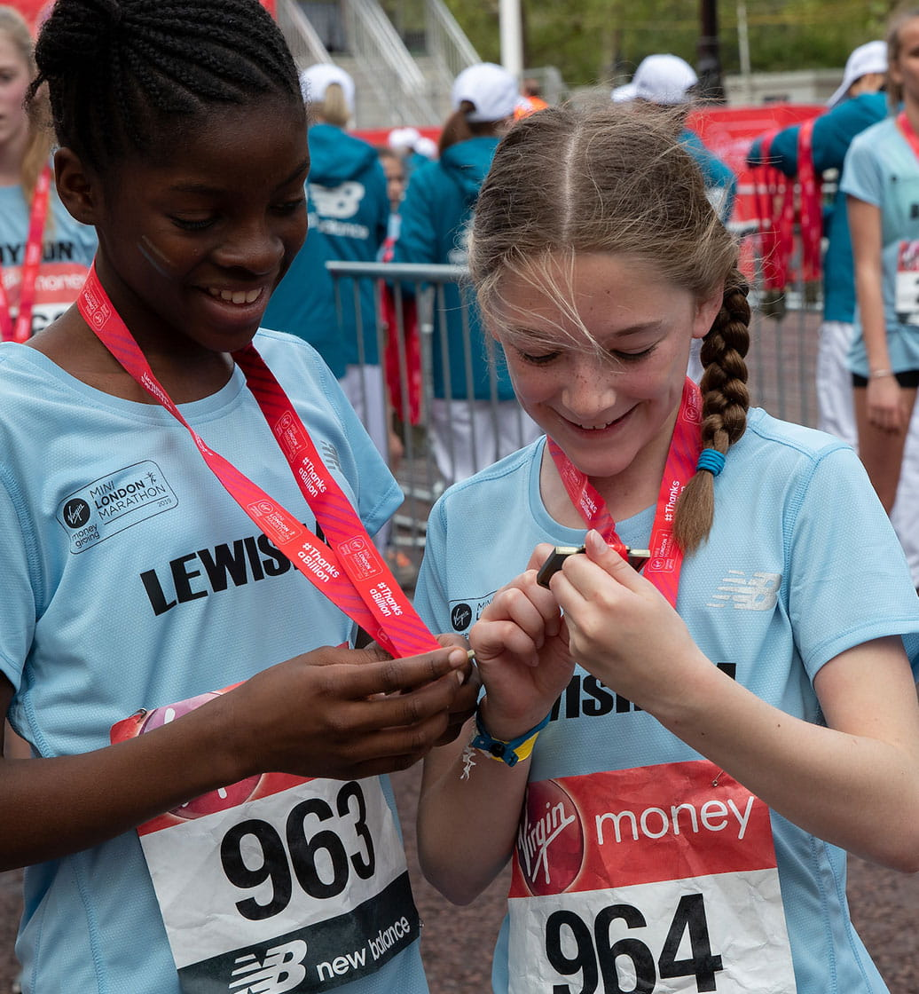 Two runners admire their medals at the Virgin Money Giving Mini London Marathon