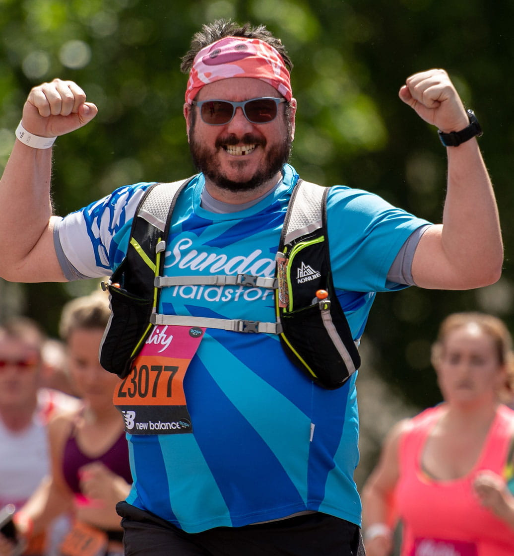 A runner flexes his muscles at the Vitality London 10,000