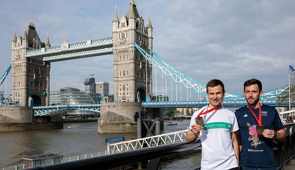 David Wyeth and Matthew Rees in front of Tower Bridge with their Virgin Money London Marathon medals