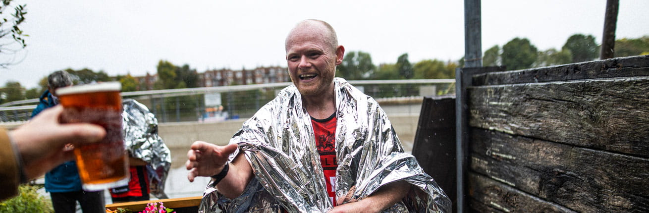 Danny Bent is handed a pint of London Pride on completing the virtual Virgin Money London Marathon in 2020
