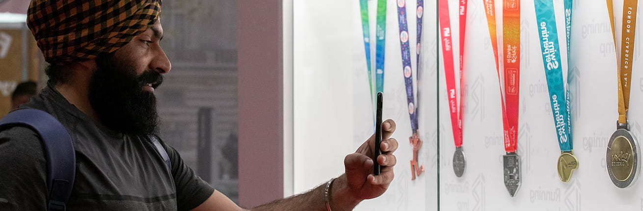A Running Show visitor takes a photo of the suite of London Marathon Events medals