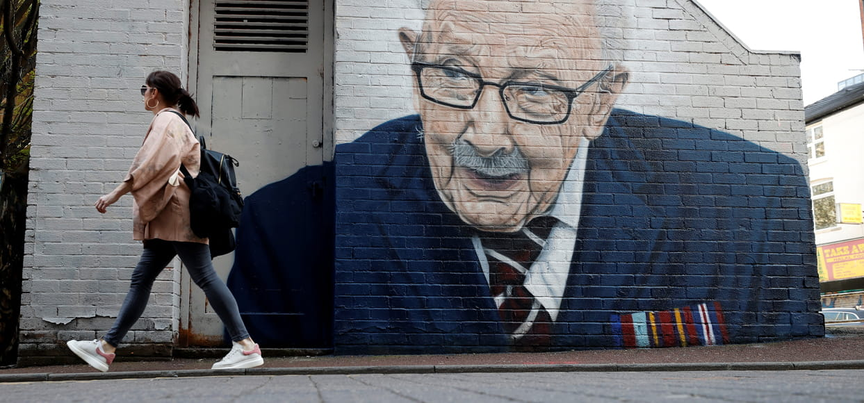 A woman walks past a new mural of British veteran and fundraiser Captain Tom Moore