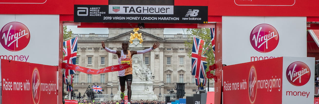 Kipchoge celebrates in front of the TAG Heuer clock after winning the 2019 Virgin Money London Marathon