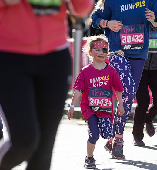 A young runner in pirate make-up completes The Little Half