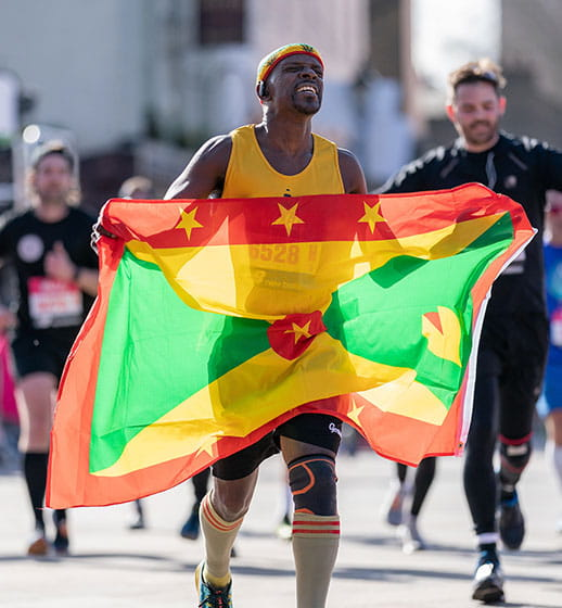 A Vitality Big Half runner with a flag of Grenada